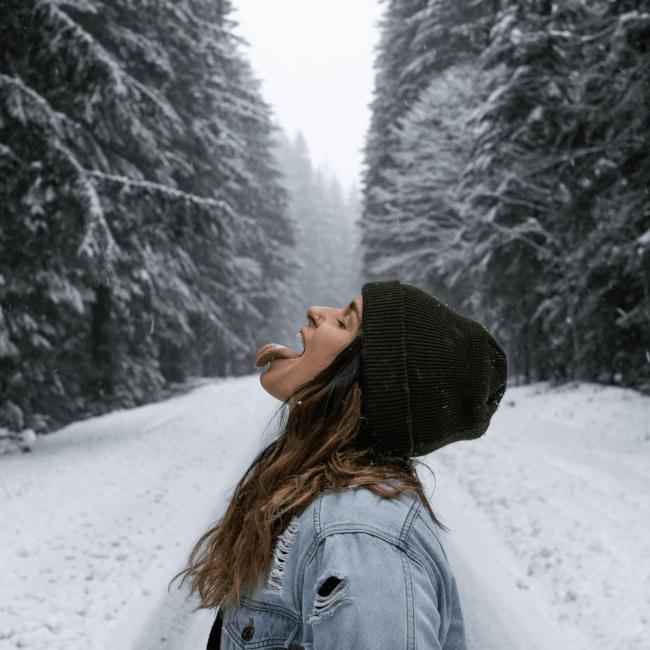 Frau in Winterlandschaft fängt Schneeflocke mit Zunge