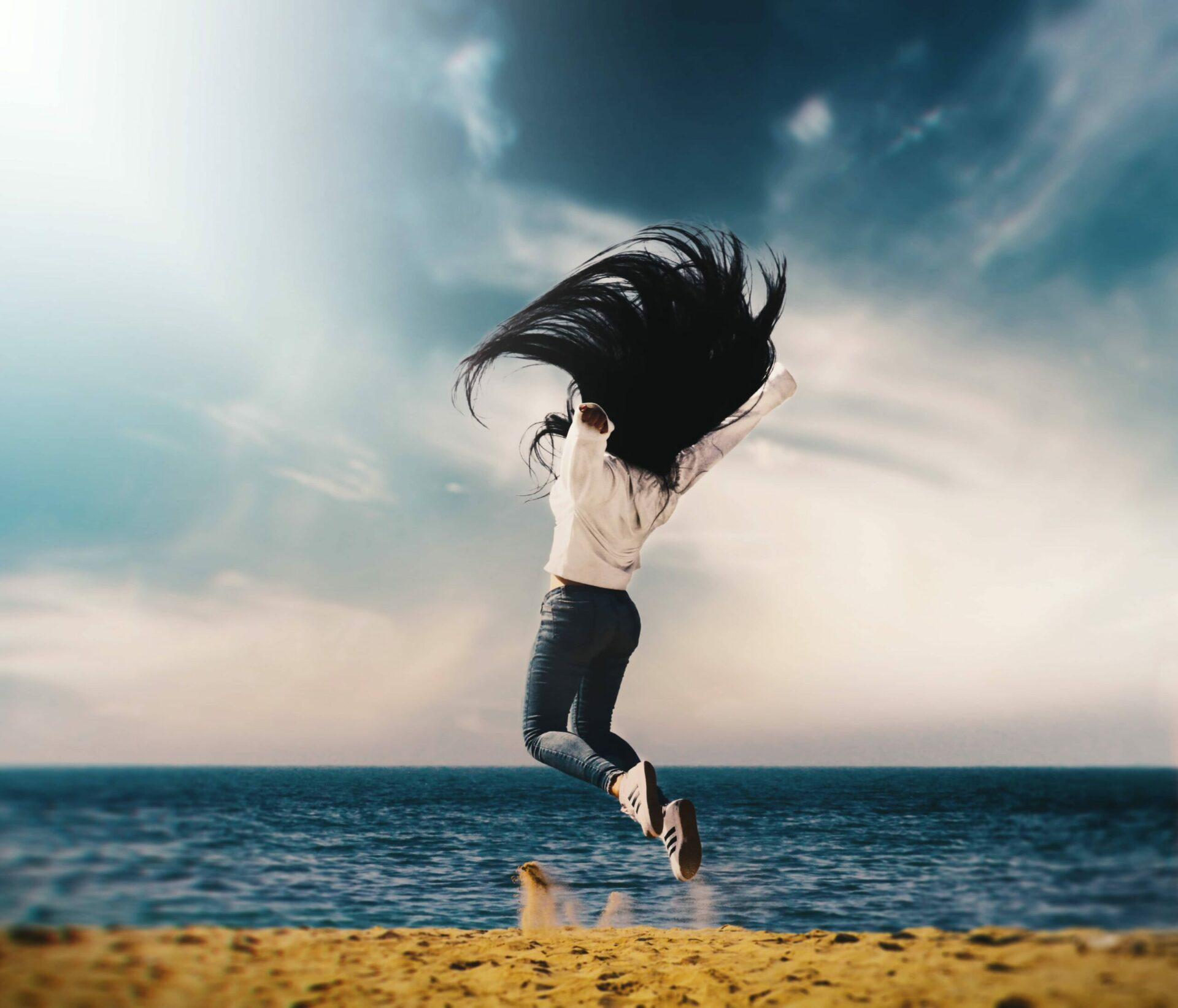 Frau springt auf Wiese mit Meer im Hintergrund