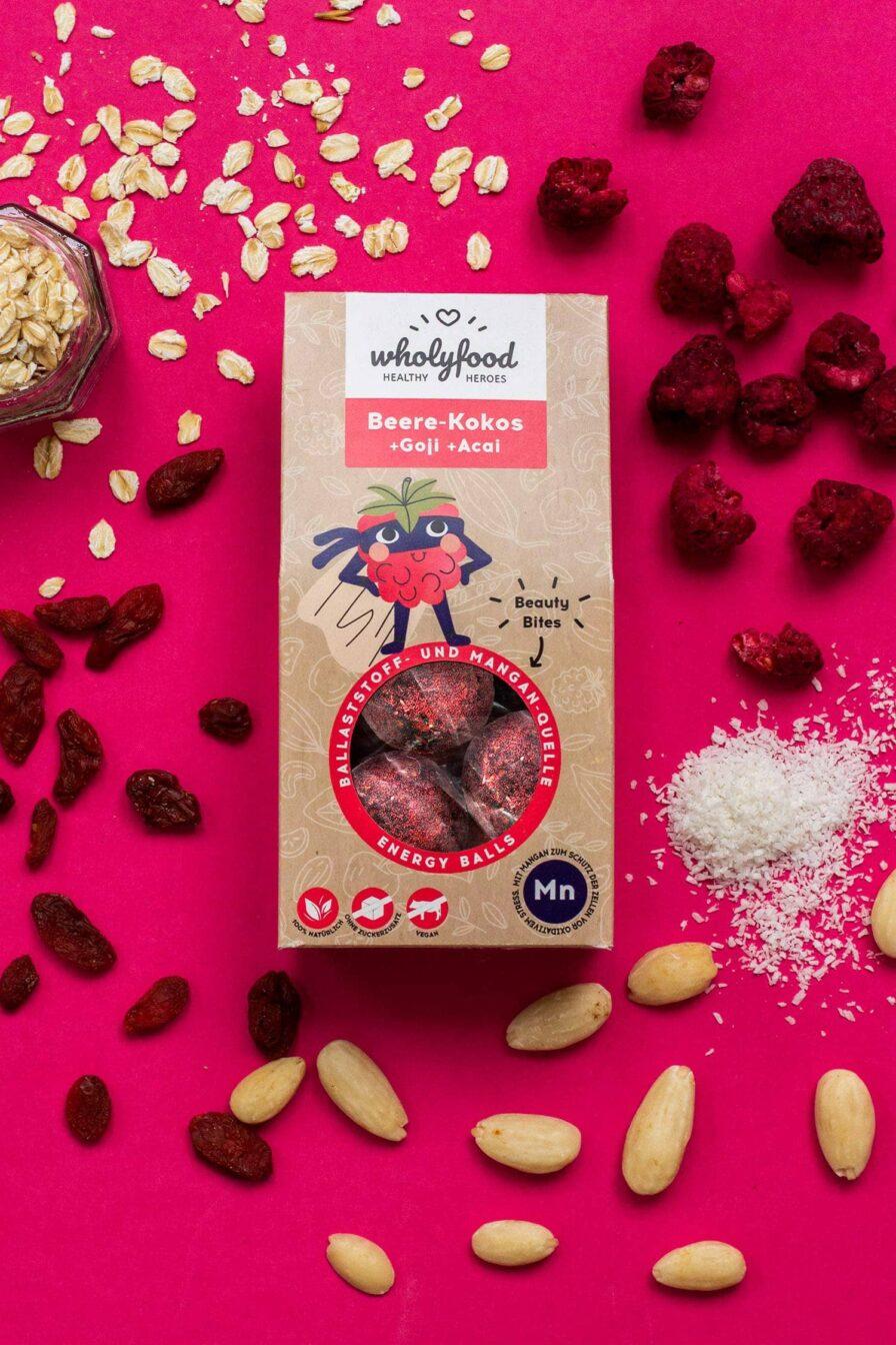 Produktbild wholyfood Energy Ball Beere-Kokos (Beauty Bites) Verpackung auf Hintergrund mit Zutaten
