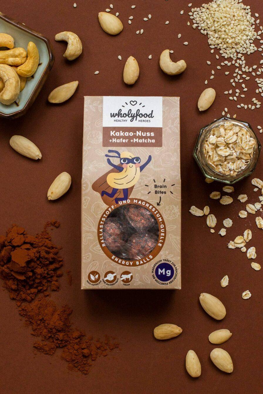 Produktbild wholyfood Energy Ball Kakao-Nuss (Brain Bites) Verpackung auf Hintergrund mit Zutaten